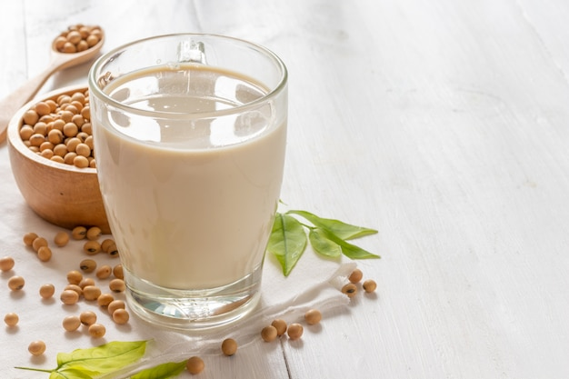 Soy or soymilk in glass with soybeans in wooden bowl Premium Photo