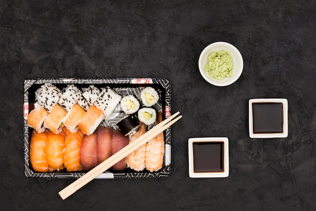 Soya sauce; wasabi and variety of fish rolls on slate backdrop Free Photo