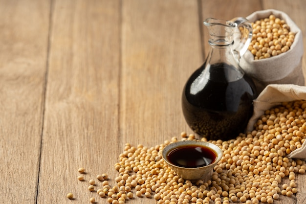 Soybean sauce and soybean on wooden floor soy sauce food nutrition concept. Free Photo