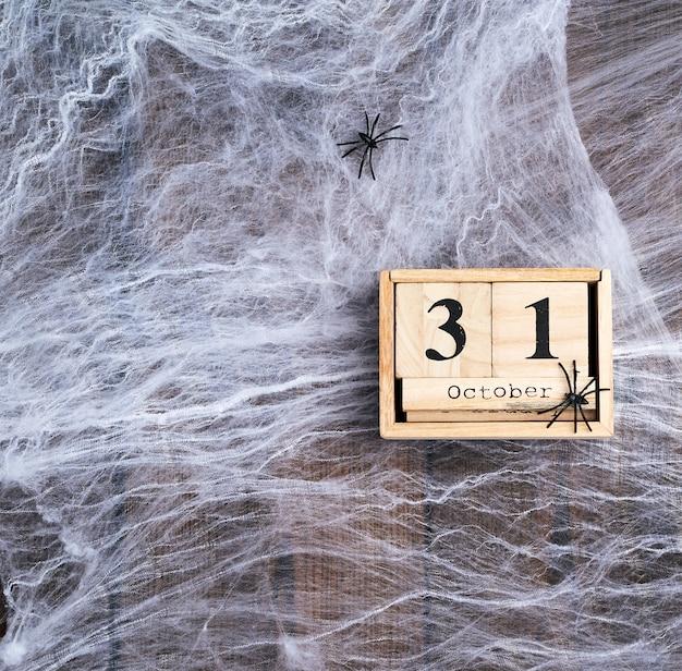 白いspの巣と10月31日の日付のブロックで作られた木製のレトロなカレンダー Premium写真