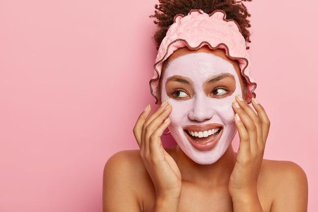 Концепция ухода за кожей и спа. довольная афроамериканка наносит на лицо питательную глиняную маску, у нее радостное выражение лица, смотрит влево, трогает щеки, борется с проблемой сухой кожи, имеет обнаженное до пояса тело. Бесплатные Фотографии