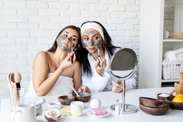 스파 및 웰빙 개념. 자가 관리. 재미 얼굴 마스크를 적용 두 아름 다운 여자 프리미엄 사진