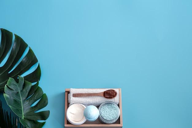Spa. articoli per la cura del corpo su uno sfondo blu con foglie tropicali. accessori estivi. spazio per il testo. Foto Gratuite