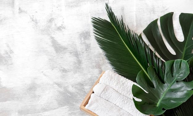 Спа. предметы ухода за телом на белом с тропическими листьями. Бесплатные Фотографии