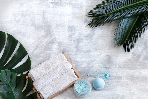 Spa. body care items on a white background with tropical leaves. summer accessories. space for text. Free Photo