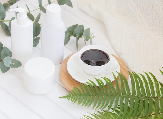 黒のコーヒーカップとクリームとシャンプーボトルの瓶のスパ組成物。 無料写真