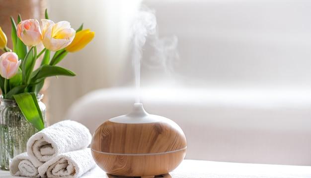 ボディケア製品を備えたモダンなオイルディフューザーの香りを持つスパ組成物。ツイスト白いタオル、春の緑と花。体と健康管理のためのスパのコンセプト。 無料写真