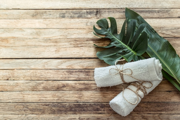 Spa composition with towels and tropical leaf on a wooden wall. Free Photo