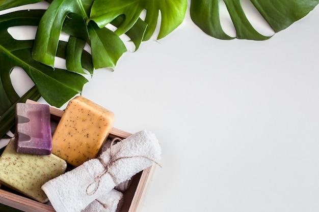 白い背景の上の熱帯の葉とスパの組成物。別の有機石鹸、ケアと美容のコンセプト、トップビュー 無料写真