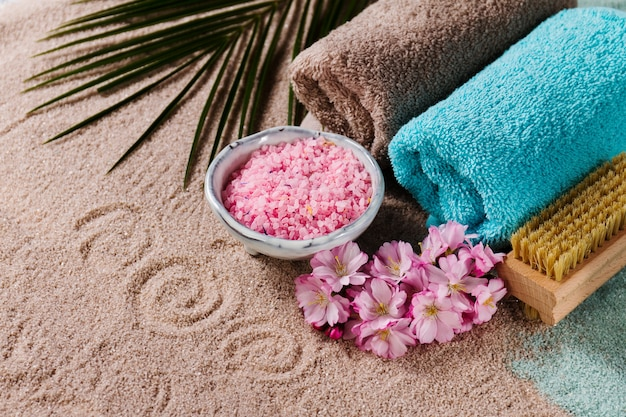 Spa concept. closeup of beautiful spa products - spa salt, towels and flowers. horizontal. Free Photo