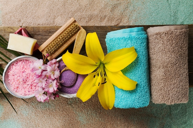 Spa Concept. Top view of beautiful Spa Products with place for text. Essential oils with beautiful flowers, towels, spa salt and hand made soap. Free Photo