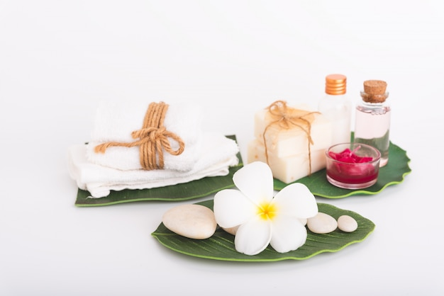 Spa concept,white stone, red candle, rose liquid soap, towel, flowers  on green leaves Premium Photo