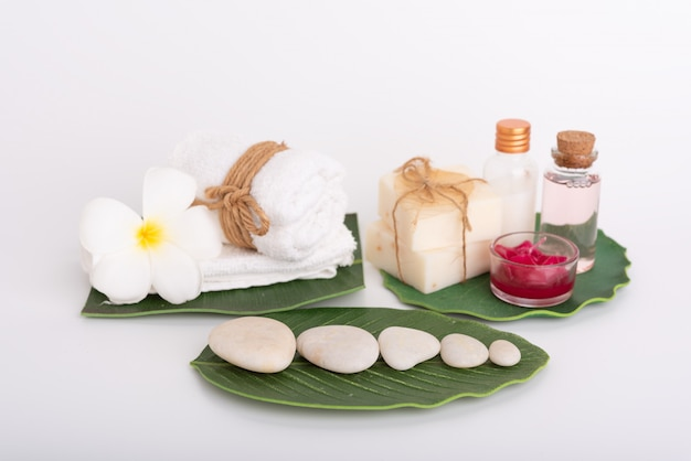 Spa concept, white stone, red candle, rose liquid soap, towel, flowers  on green leaves Premium Photo