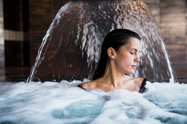 Spa concept with woman relaxing in water Free Photo