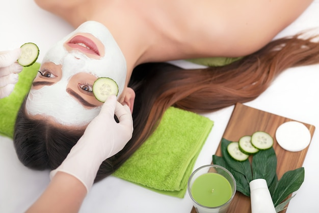 Spa concept. young woman with nutrient facial mask in beauty salon, close up Premium Photo