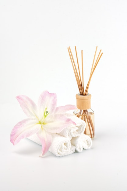 Spa decoration with pink lily, white towels and aroma oil Premium Photo
