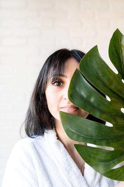 스파 페이셜 마스크. 스파와 아름다움. 그녀의 얼굴 앞에 녹색 몬스 테라 잎을 들고 목욕 가운을 입고 행복 한 아름 다운 갈색 머리 중동 여자 프리미엄 사진