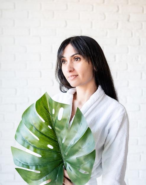 스파 페이셜 마스크. 스파와 아름다움. 녹색 Monstera 잎을 들고 목욕 가운을 입고 행복 한 아름 다운 갈색 머리 중동 여자 프리미엄 사진