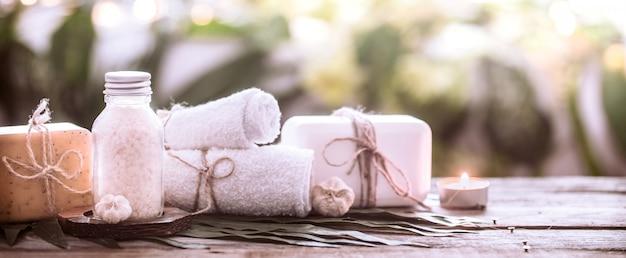 白いタオルと海の塩、キャンドルの木製の背景を持つ熱帯の葉の組成を持つスパ手作り石鹸 無料写真