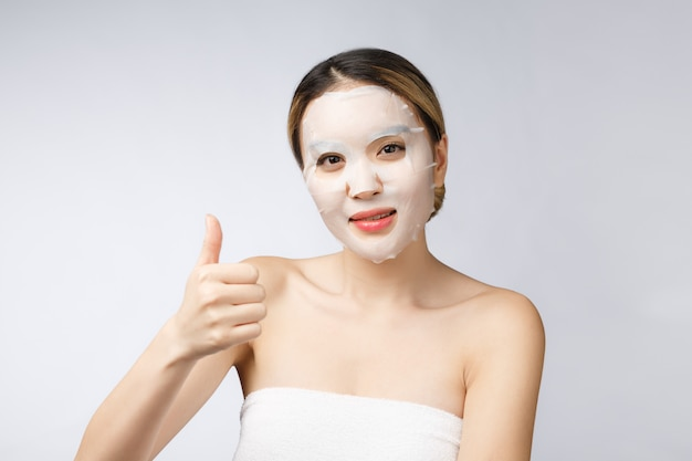 Spa, healthcare. asian girl with a cosmetic mask with showing thumb up. Premium Photo