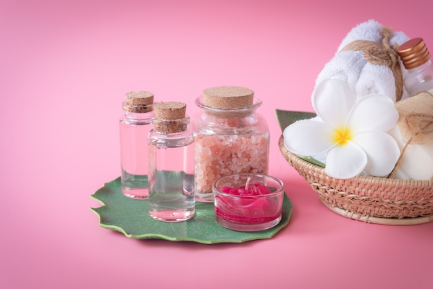 Spa  himalayan salt, red candle, milk  and rose liquid soap, white towel, flowers  set on green leaves over pink Premium Photo