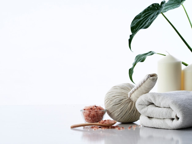 Spa massage concept, herbal compress ball, cream, flower soap, scented candle and himalayan pink salt, isolated Premium Photo