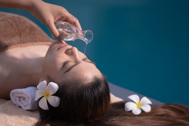 Spa massage therapy and body with oil beside the pool. Premium Photo