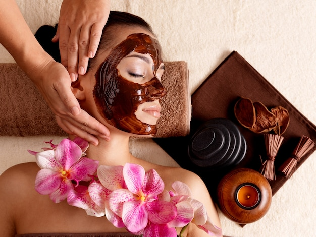 Spa massage for young woman with facial mask on face - indoors Free Photo