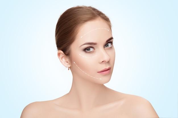 파란색 배경 위에 그녀의 얼굴에 화살표가있는 매력적인 여자의 스파 초상화. 얼굴 리프팅 개념. 성형 외과 치료, 의학 프리미엄 사진