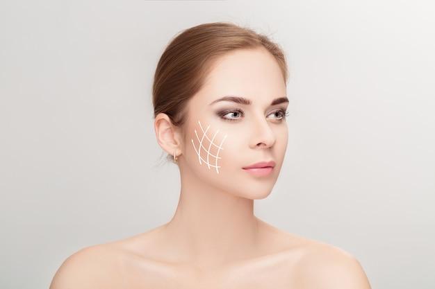 회색 배경 위에 그녀의 얼굴에 화살표가있는 매력적인 여자의 스파 초상화. 얼굴 리프팅 개념. 성형 외과 치료, 의학 프리미엄 사진