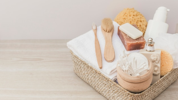 Spa products with brushes and loofah in tray on wooden backdrop Free Photo