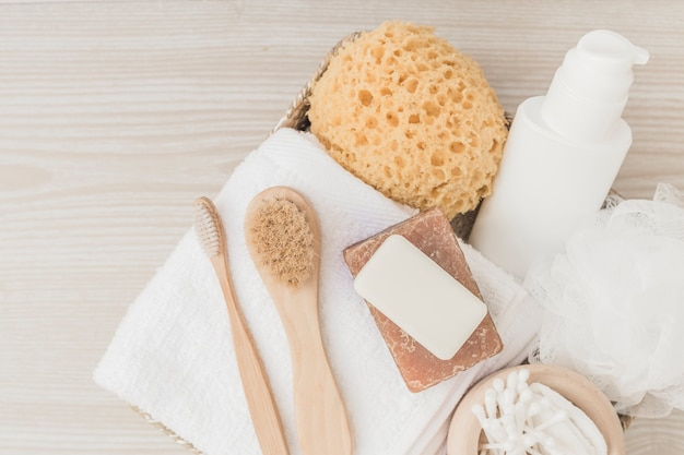 Spa products with brushes and loofah on wooden background Free Photo