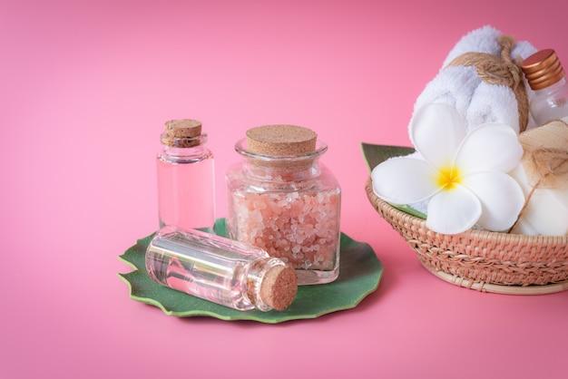 Spa salt, milk  and rose liquid soap, white towel, flowers  set on green leaves Premium Photo