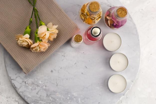 スパセット、ボトル、キャンドル、花のトップビュー大理石の背景コピースペース Premium写真