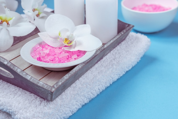 Spa setting still life with orchid flower , candle, soap and towels on blue background Premium Photo
