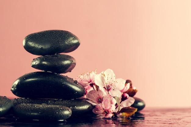 Красивые розовые цветы spa на горячих камнях spa на фоне влажной воды. боковая композиция. копирование пространства. концепция курорта. темный фон. Бесплатные Фотографии