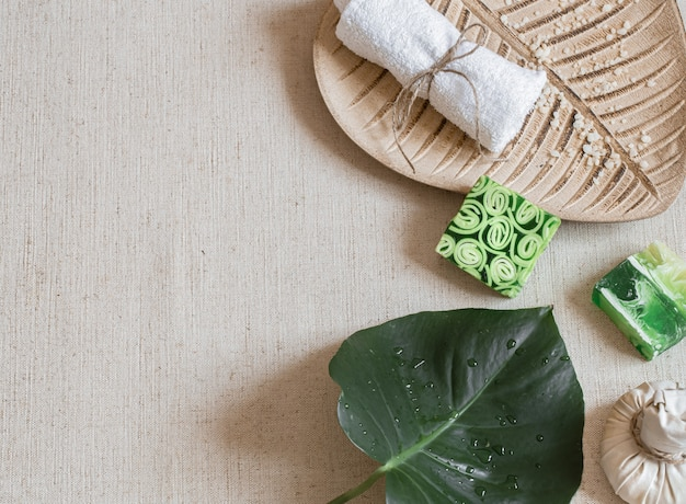 Spa still life with soap, towel, leaf and sprinkled sea salt top view. hygiene and beauty concept. Free Photo