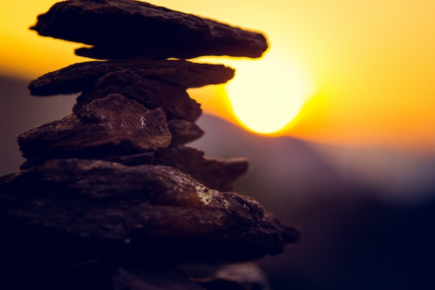 Spa stones balance, colorful summer sky , silhouette of stacked pebbles and butterfly, beautiful nature, peaceful beach sunset, ual image of stable life Premium Photo