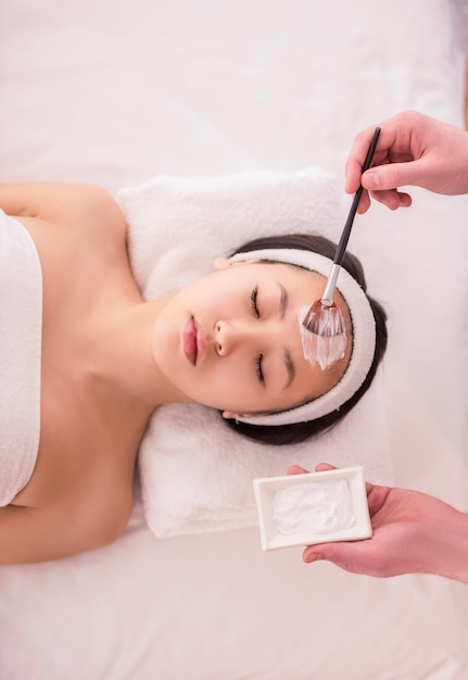 Spa therapy for asian woman receiving facial mask. Premium Photo