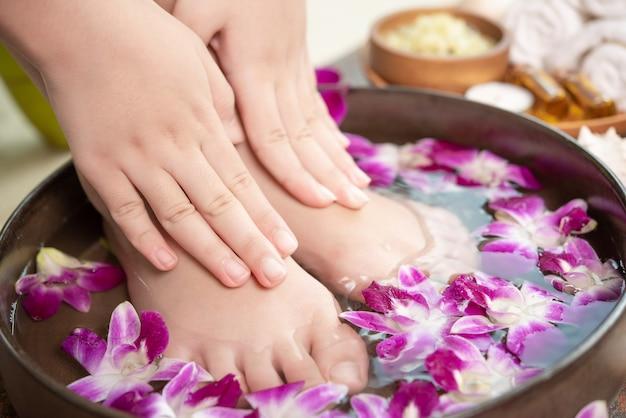 Trattamento termale e prodotto per piedi femminili e spa per le mani. fiori di orchidea in ciotola di ceramica. Foto Gratuite