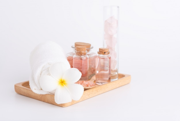 Spa treatment with liquid soap, pink salt, stones and plumeria flower on wood tray over white Premium Photo