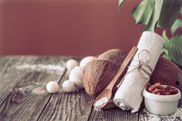 Spa e centro benessere con fiori e asciugamani. composizione luminosa sul tavolo marrone con fiori tropicali. posto per il testo. noce di cocco Foto Gratuite