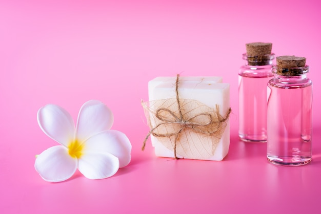 Spa wellness with milk soap, rose oil bottle and beautiful white plumeria flower Premium Photo