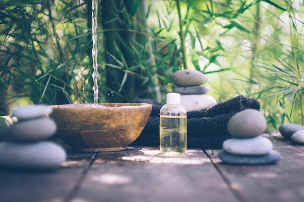 Spa with woman hands and clear water on an old wood Premium Photo