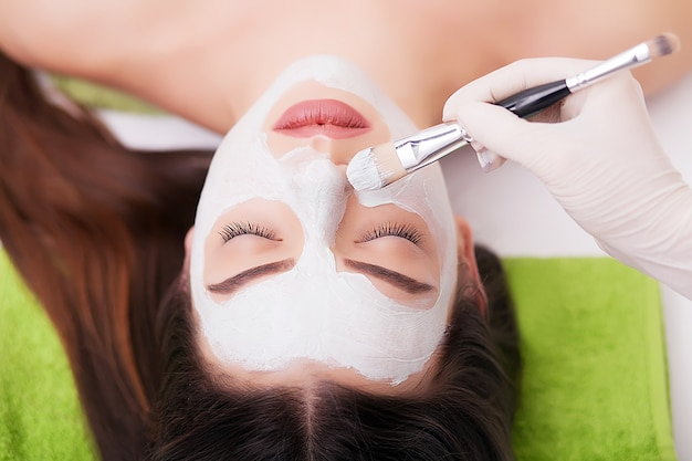 Spa woman applying facial cleansing mask. beauty treatments. clay mask Premium Photo