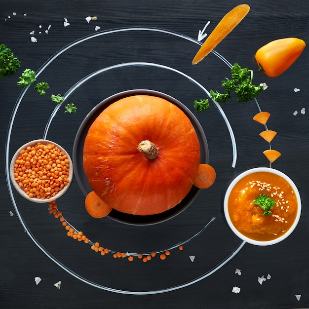 Space pumpkin solar system with orange vegetables, flat lay concept of healthy food background Premium Photo