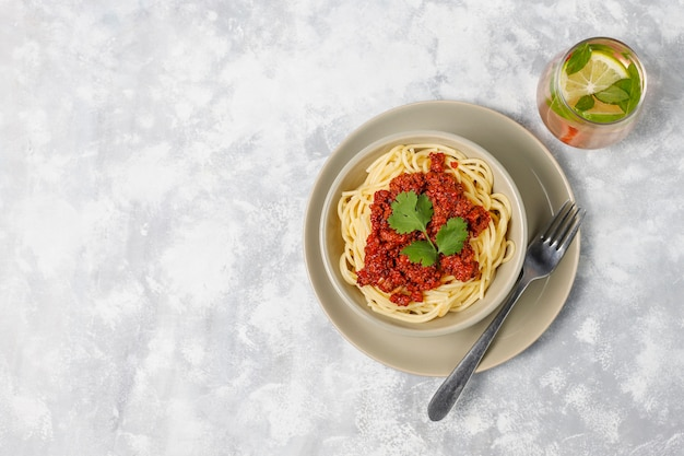 Spaghetti bolognese and lemonade on grey concrete Free Photo
