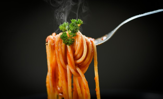 Spaghetti on fork and black background Premium Photo