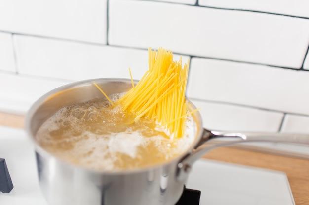 ガスコンロの熱湯で調理する鍋のスパゲッティ。黄色のグルテンフリーコーンパスタ Premium写真