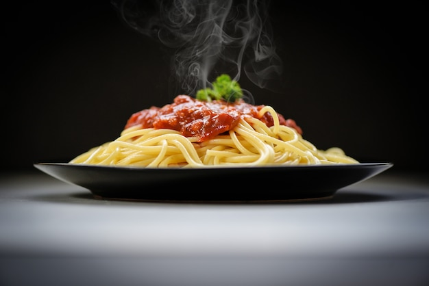 Spaghetti italian pasta served on black plate with tomato sauce and parsley in the restaurant italian food and menu concept. spaghetti bolognese on black Premium Photo
